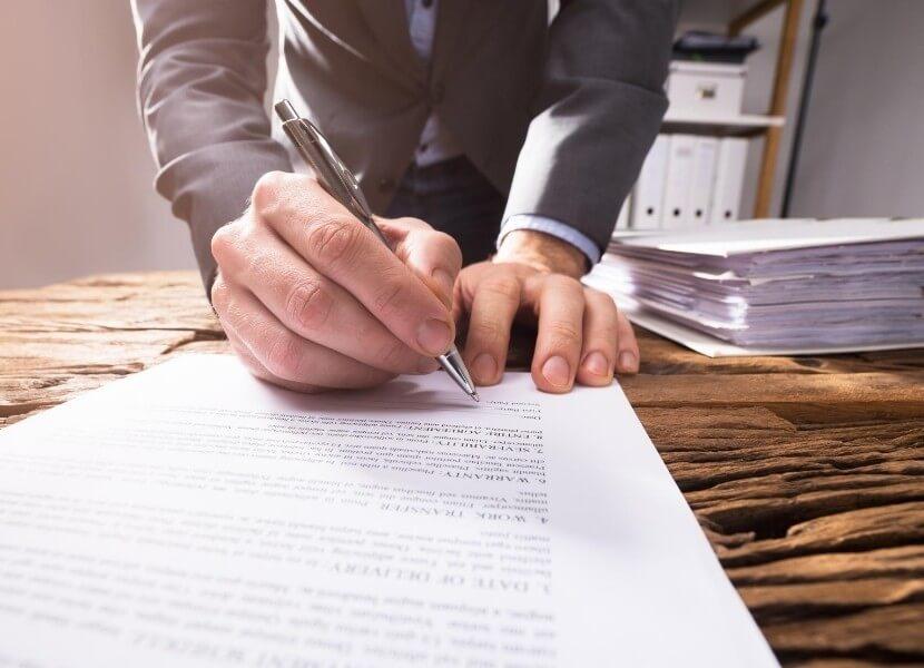 mężczyzna podpisujący dokkumenty
